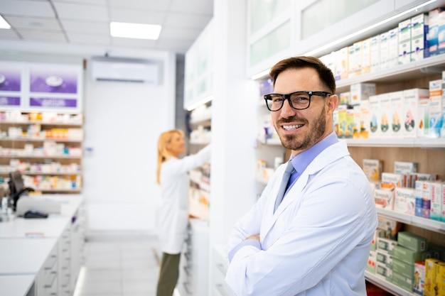 Retrato de sorridente farmacêutico caucasiano em pé na farmácia com os braços cruzados.
