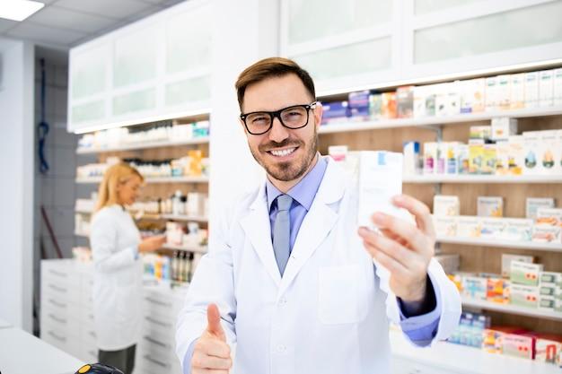 Retrato de sorridente farmacêutico caucasiano segurando vitaminas na farmácia.