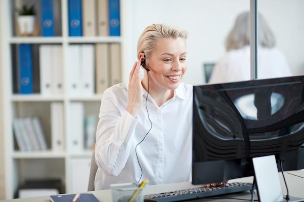 Retrato de sorridente gerente feminina usando fone de ouvido enquanto trabalhava como operadora de relacionamento com o cliente no interior do escritório