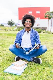 Retrato, de, sorrindo, africano, estudante masculino, sentando, ligado, a, grama verde, segurando, livro, em, a, mão