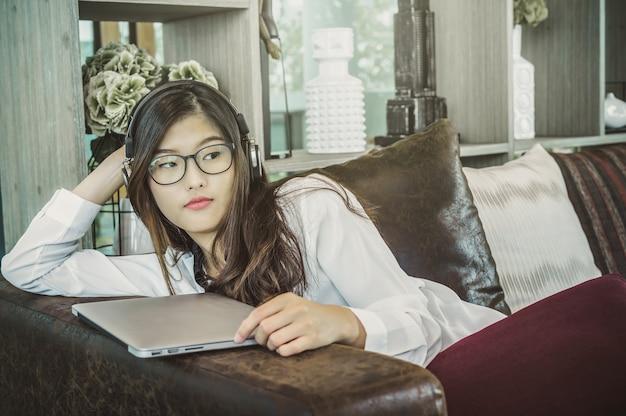 Retrato, de, sorrindo, asiático, bonito, jovem, executiva, escutar música, com, fone ouvido