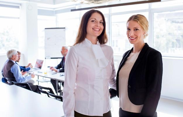 Retrato, de, sorrindo, dois, mulher negócios fica, frente, empregados, trabalhando, escritório