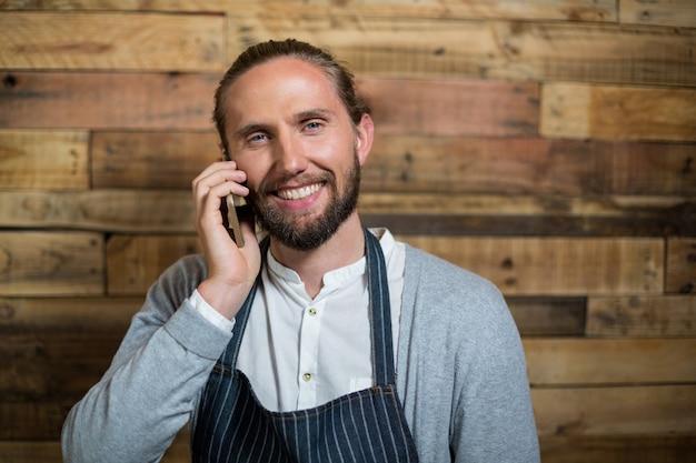 Retrato, de, sorrindo, garçom, falando telefone móvel, contra, parede madeira