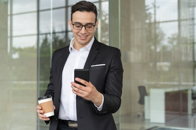 Retrato, de, sorrindo, homem negócios, com, café, leitura, mensagem