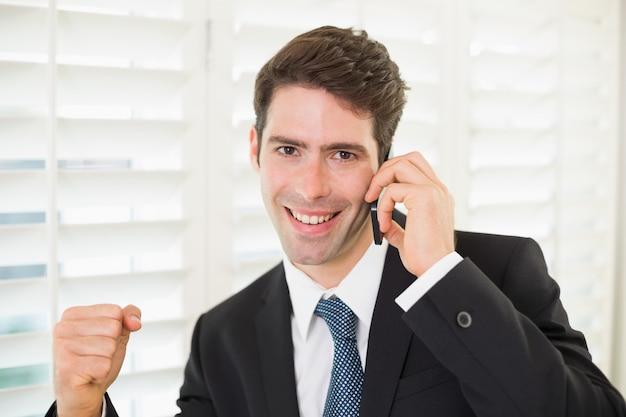 Retrato, de, sorrindo, homem negócios, usando, telefone móvel, enquanto, clenching, punho