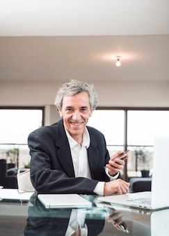 Retrato, de, sorrindo, homem sênior, com, tablete digital, e, laptop, ligado, vidro, refletivo, escrivaninha