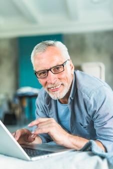 Retrato, de, sorrindo, homem sênior, usando computador portátil