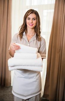 Retrato, de, sorrindo, hotel jovem, empregada, segurando, pilha, de, fresco, limpo, toalhas, em, a, sala