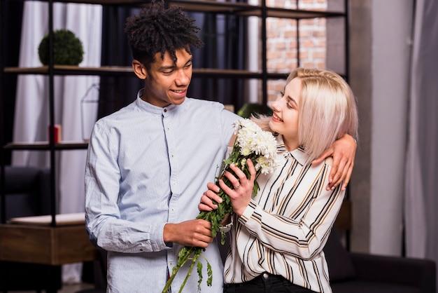 Retrato, de, sorrindo, interracial, par jovem, segurando, flor branca, buquet