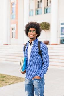 Retrato, de, sorrindo, jovem, macho afro, estudante, segurando, livros, em, mão, ficar, contra, universidade, predios