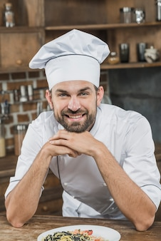 Retrato, de, sorrindo, jovem, macho profissional, cozinheiro, com, seu, prato preparado