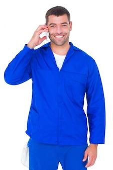 Retrato, de, sorrindo, macho, mecânico, usando, telefone móvel