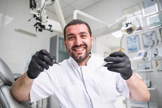 Retrato, de, sorrindo, macho, odontólogo, com, dental, ferramentas