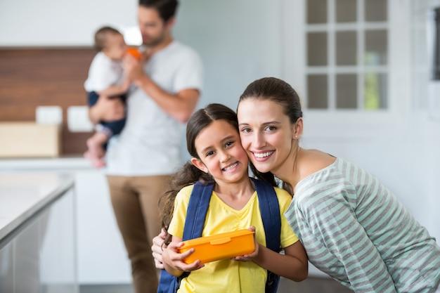 Retrato, de, sorrindo, mãe filha, segurando lancheira