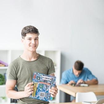 Retrato, de, sorrindo, menino adolescente, segurando, motherboard