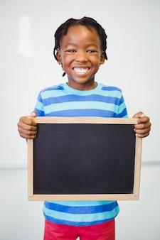 Retrato, de, sorrindo, menino escola, segurando, ardósia, em, sala aula