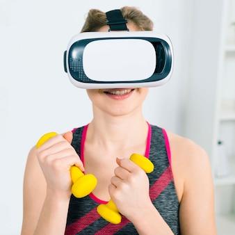 Retrato, de, sorrindo, mulher jovem, desgastar, virtual, realidade, headset, segurando, amarela, dumbbells