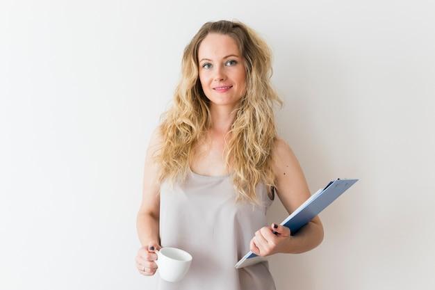 Retrato, de, sorrindo, mulher jovem, segurando clipboard, e, branca, xícara café