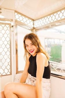 Retrato, de, sorrindo, mulher jovem, sentando, em, a, roda ferris, cabana