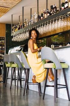 Retrato, de, sorrindo, mulher jovem, sentando, em, barra, contador, segurando, cellphone