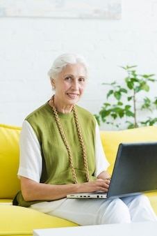 Retrato, de, sorrindo, mulher jovem, sentar sofá amarelo, com, laptop