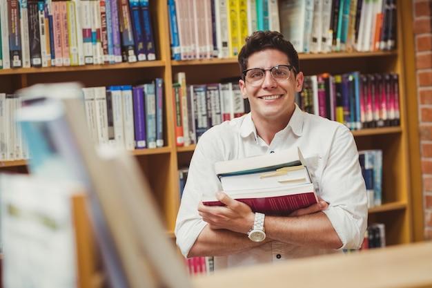 Retrato, de, sorrindo, nerd, segurando, livros, em, biblioteca