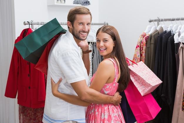 Retrato, de, sorrindo, par, com, bolsas para compras, abraçar
