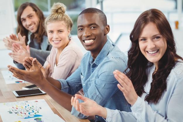 Retrato, de, sorrindo, pessoas negócio, aplaudindo, escrivaninha, em, escritório