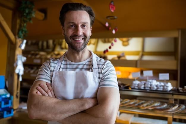 Retrato de sorrindo proprietário pé na padaria