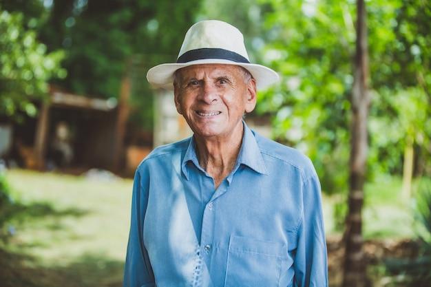 Retrato de sorrir mais velho agricultor masculino com chapéu