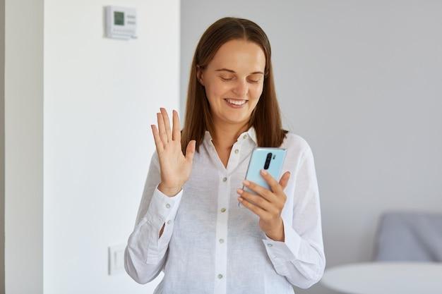 Retrato de sorrir morena jovem adulto feminino, vestindo camisa branca em pé em casa com o telefone nas mãos, tendo a videochamada, acenando com a mão para a câmera do dispositivo.