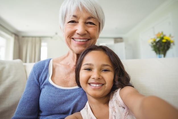 Retrato de sorrir neta e avó sentado no sofá na sala de estar