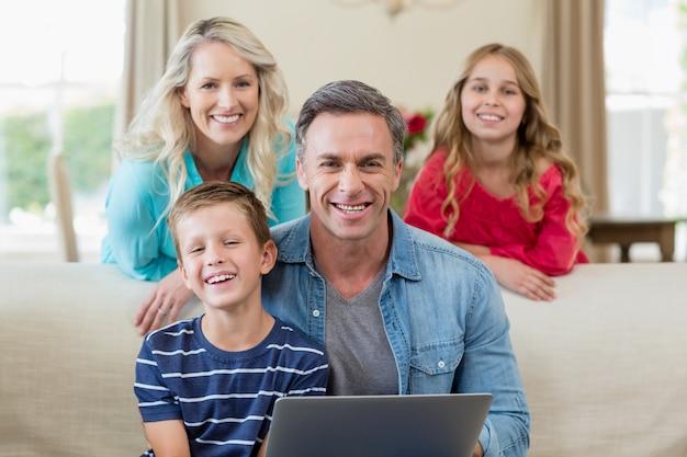 Retrato de sorrir pais e filhos com o laptop na sala de estar