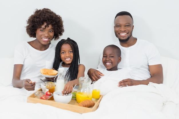 Retrato de sorrir pais e filhos tomando café da manhã no quarto