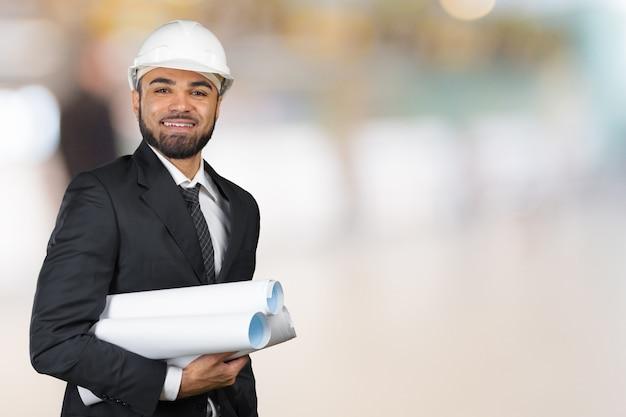 Retrato de sorriso confiante do arquiteto preto segurando planos isolados no estúdio