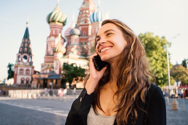 Retrato de sorriso da jovem mulher no quadrado vermelho que fala no telefone, com a catedral da manjericão de saint no fundo. moscou, rússia.