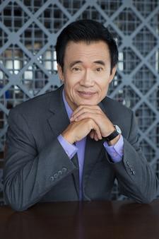 Retrato de sorriso do homem asiático com as mãos no queixo