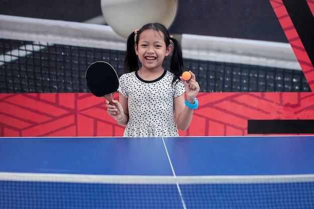 Retrato de sorriso menina asiática jogar ténis de mesa