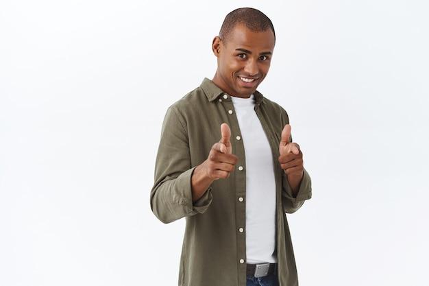 Retrato de sortudo homem afro-americano confiante parabenizando pessoa, apontando pistolas de dedo na frente