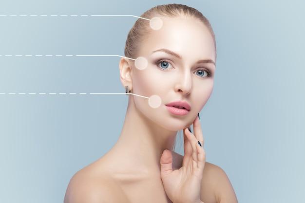 Retrato de spa de mulher jovem e natural com setas pontilhadas no rosto sobre fundo azul. remédios e cuidados com a pele