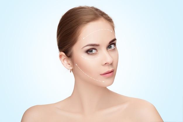 Retrato de spa de uma mulher atraente com setas no rosto sobre fundo azul. conceito de levantamento de rosto. tratamento de cirurgia plástica, medicamentos