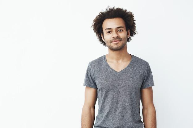 Retrato de stong e bonito homem africano sorrindo posando sobre parede branca. estudante confiante ou dono de loja.
