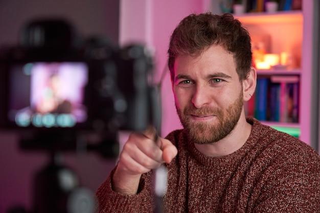 Retrato de streamer transmitindo e apontando para a câmera com o dedo