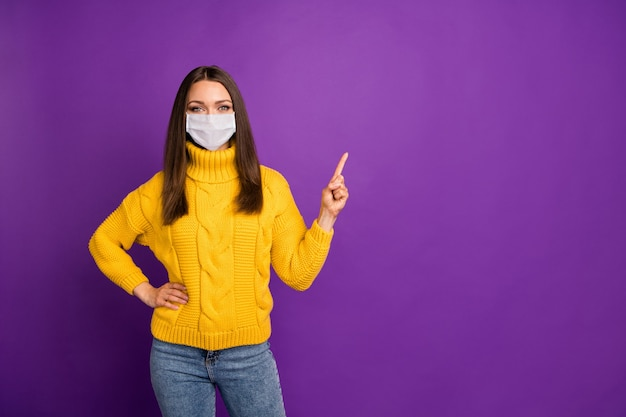 Retrato de sua garota atraente usando máscara de gaze demonstrando cópia de espaço descontaminação cobre síndrome de influenza pneumonia risco de febre gripe isolado em fundo de cor violeta