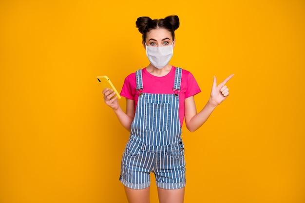 Retrato de sua garota legal usando celular usando máscara de segurança demonstrando infecção cov cópia espaço estatística de novidade comprar seguro isolado brilhante brilho vívido fundo de cor amarela vibrante