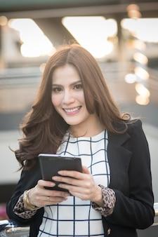 Retrato, de, sucedido, esperto, mulher negócio, olhar, confiante, e, sorrindo, segurando, tabuleta, computador