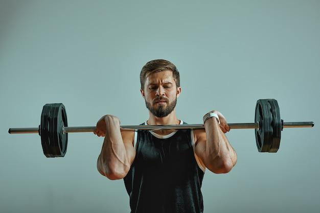 Retrato de super apto muscular jovem malhando na academia com barra em fundo cinza