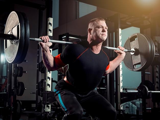 Retrato de super apto muscular jovem malhando na academia com barra