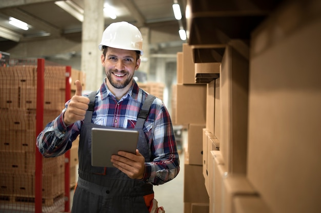 Retrato de supervisor de armazém organizando com sucesso a distribuição e remessa de mercadorias de um grande depósito para o mercado.