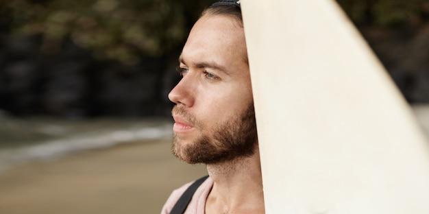 Retrato de surfista masculino se preparando para conquistar ondas poderosas gigantes